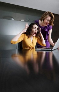 Two business executives reacting in shock at laptop