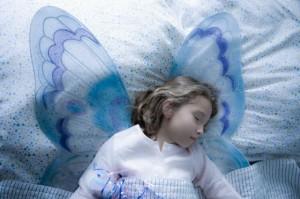 Girl (7-9) in fairy costume sleeping
