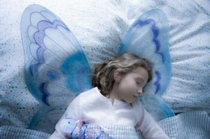 Girl (7-9) in fairy costume sleeping