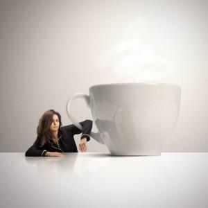 Sleepy woman holding huge cup of coffee