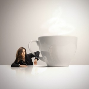Sleepy woman holding huge cup of coffee