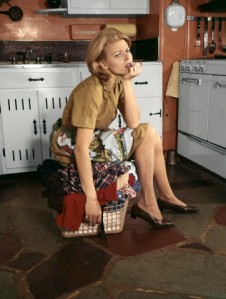 1960s TIRED HOUSEWIFE SITTING ON TOP OF LAUNDRY BASKET IN KITCHEN