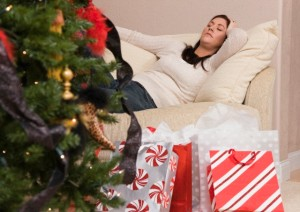 Tired woman resting on couch behind Christmas tree