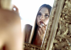 Young woman putting some lipstick on in front of a mirror