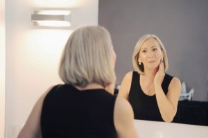 Senior woman looking at reflection in mirror