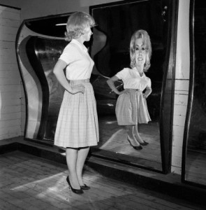 Woman Standing at Fun House Mirror