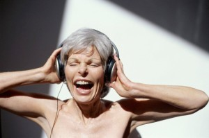Female senior with headphones holding head in hands