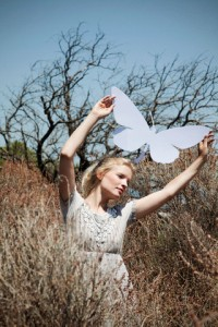 Young woman holding paper butterfly outdoors