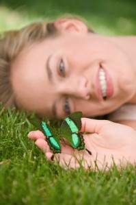 Close up of woman laying in grass holding butterfly