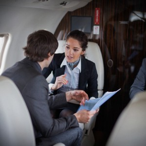 Businesspeople on a jet plane discussing business