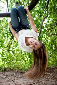 Young woman hanging upside down on tree branch