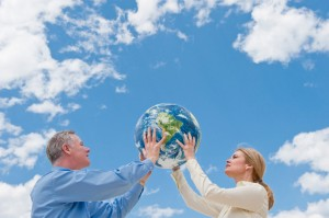 Two people holding up a globe