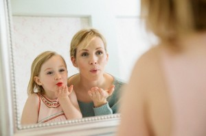 Mother looking at daughter (4-5) applying lipstick