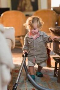 Caucasian baby boy vacuuming living room rug