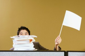 Businessman waving white flag --- Image by © Monalyn Gracia/Corbis
