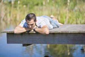 Germany --- Young man relaxing on wooden jetty --- Image by © Hoffmann Photography/ /age fotostock Spain S.L./Corbis