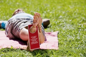 Man lying on picnic blanket, sleeping with Do Not Disturb sign on his foot --- Image by © RelaXimages/Corbis