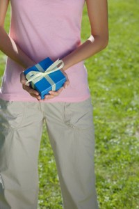 Young woman holding blue present with yellow ribbon in her hands --- Image by © RelaXimages/Corbis