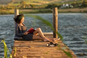Woman reading book on dock --- Image by © Zero Creatives/cultura/Corbis