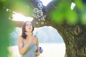 Low angle view of mid adult woman blowing bubbles in woodland --- Image by © Daniel Ingold/Corbis