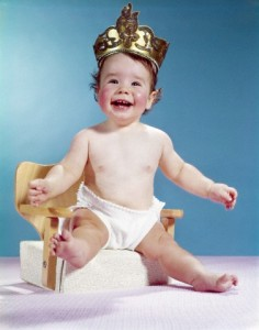 24 Jun 1964 --- 1960s SMILING HAPPY BABY WEARING CROWN SITTING ON BOOSTER SEAT CHAIR THRONE LOOKING AT CAMERA --- Image by © H. ARMSTRONG ROBERTS/Corbis