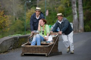 Portugal --- Woman enjoys her ride on the Monte Toboggan Run, Funchal, Madeira, Portugal --- Image by © Holger Leue/Corbis